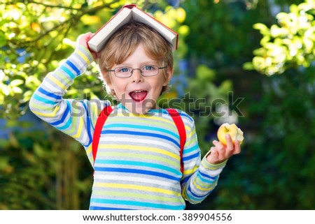 Happy little kid boy with glasses, books, apple and backpack on his first day to school or nursery. Child outdoors on warm sunny day, Back to school concept - stock photo
