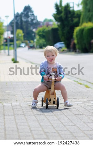 Happy little kid, cute blonde toddler girl playing outdoors on the street riding her push bike, wooden horse with wheels, on a sunny summer day