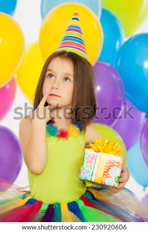 Happy little kid girl with gift box and colorful balloons on birthday party. Holidays, birthday concept. - stock photo