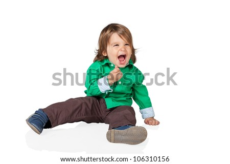 Happy little kid, 2 years old boy, sitting on the floor and laughing out loud, wearing shirt and jeans. High resolution image isolated on white background with copy space. Studio shot.