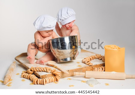 Happy little kids with chef hats preparing a cake or pizza dough, mixing ingredients. Studio shot with kitchen tools and flour. - stock photo