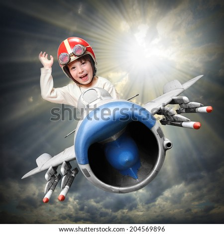 Happy little pilot flying in retro jet fighter. - stock photo