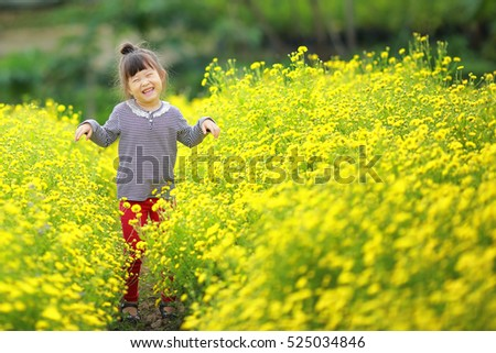 Happy little pretty girl in yellow flower field