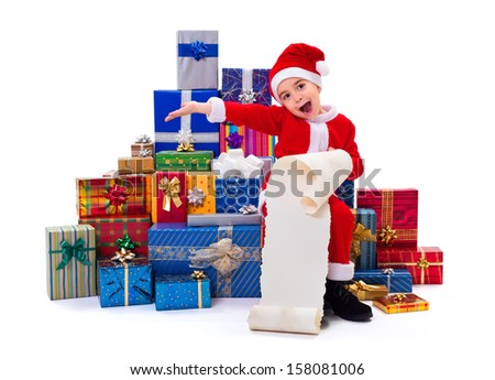 Happy little Santa Claus boy along gifts, holding wish list - stock photo