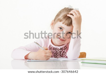 Happy little school girl learning to write, white background - stock photo
