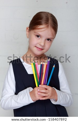 Happy little schoolgirl holds a lot of colored pencils