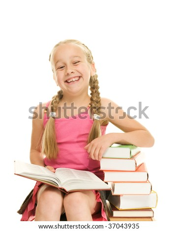 Happy little schoolgirl sitting on a stack of books - stock photo