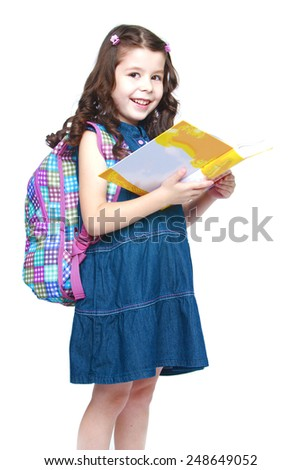 Happy little schoolgirl with backpack reading a book.Isolated on white background, Lotus Children's Center - stock photo