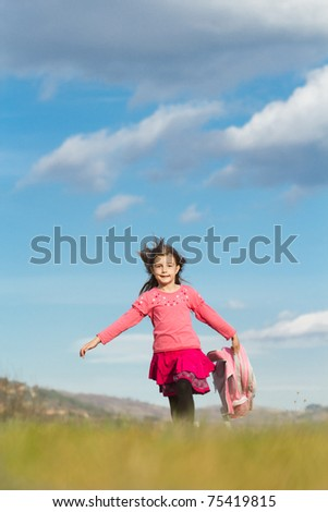 Happy little schoolgirl with bag running on fied - stock photo