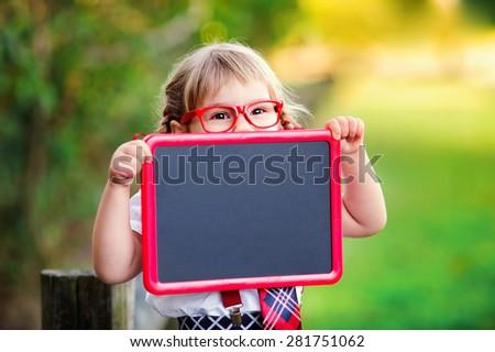 Happy little schoolgirl with chalkboard going back to school outdoor - stock photo