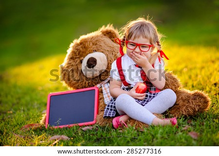 Happy little schoolgirl with chalkboard, health lunch and teddy bear back to school outdoor - stock photo