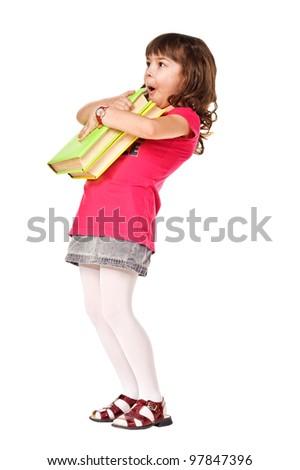 Happy little schoolgirl with heavy books. Isolated over white - stock photo