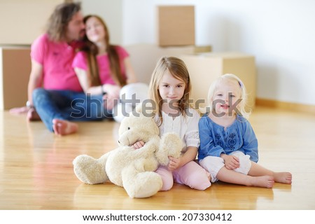 Happy little sisters with a toy and their parents in a background in their new home - stock photo