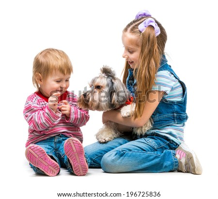 Happy little sisters with the dog Yorkshire Terrier isolated on white