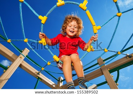 Happy little three years old child clime in the rope web on playground with sky on background - stock photo