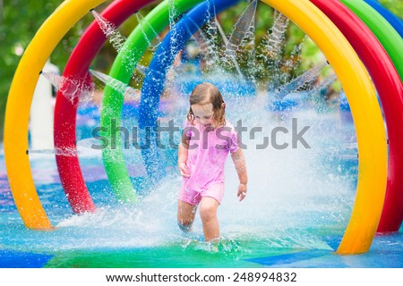 Happy little toddler girl running through a fountain having fun with water splashes in a swimming pool enjoying day trip to an aqua amusement park during summer family vacation - stock photo