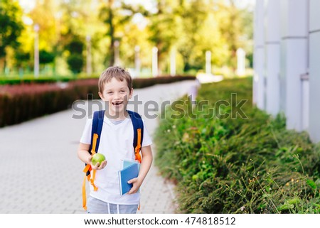 Happy little 7 years old boy at his first day at school . Dressed in white t shirt. Boy holding apple and blue book. Blue backpack