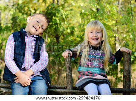 Happy Little Young Kids in an Autumn Style Outfits Sitting on the Wooden Garden Fence. - stock photo