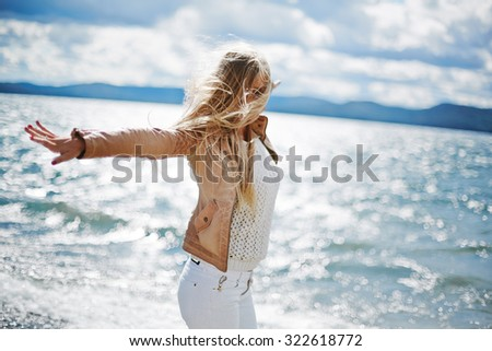 Happy long-haired girl standing with outstretched arms by the seaside - stock photo