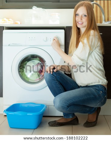 Happy long-haired woman loading clothes into the washing machine  in home