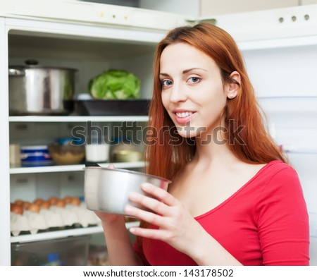 Happy long-haired woman with small pan near opened refrigerator in kitchen at home