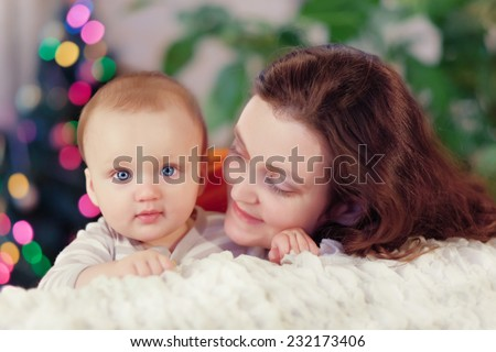 happy-looking baby and mother near Christmas tree - stock photo
