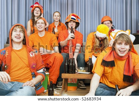 Happy looks on the faces of the fans watching a sports game at home - stock photo