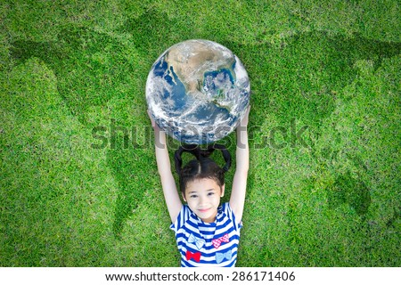 Happy lovely kid carrying a blue marble planet globe lying on the world map grass : International youth concept : Children in green environment concept: Elements of this image furnished by NASA - stock photo