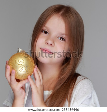 Happy lovely little girl playing with Christmas balls on gray background