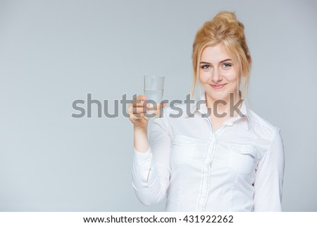 Happy lovely young businesswoman holding glass of water over white background - stock photo