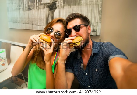 Happy lovers,attractive woman and man traveling in tropical island enjoying romance. Attractive couple making selfie,smiling and have fun together.Couple Eating big burgers,cheeseburger and coke.fun - stock photo