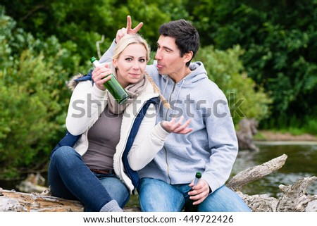 Happy lovers in vacation sitting at waterside on a trunk clinking beer bottles - stock photo