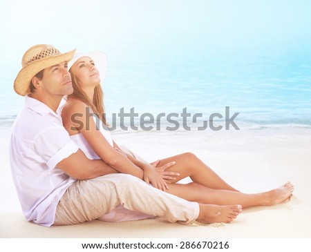 Happy lovers on the beach, beautiful young couple sitting on sandy coast and hugging, dreamy looking up in the sky and enjoying romantic honeymoon
