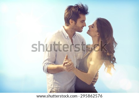 Happy loving couple embracing and kissing outdoors at summertime under blue sky. - stock photo
