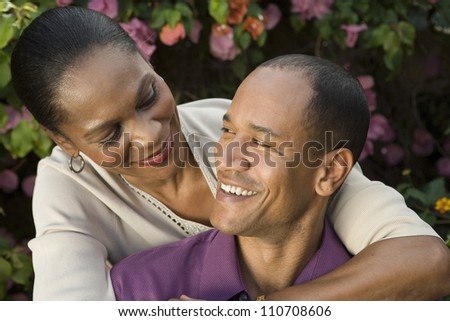 Happy loving couple embracing while looking at each other - stock photo