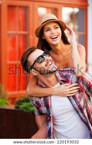 Happy loving couple. Happy young man carrying his beautiful girlfriend on shoulders and smiling while walking by the street - stock photo