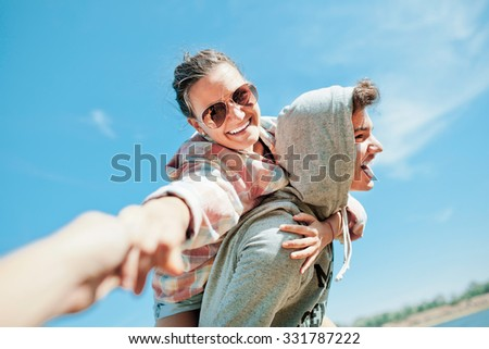 Happy loving couple. Happy young man piggybacking his girlfriend. Cheerful laughing hipsters on blue sky background - stock photo