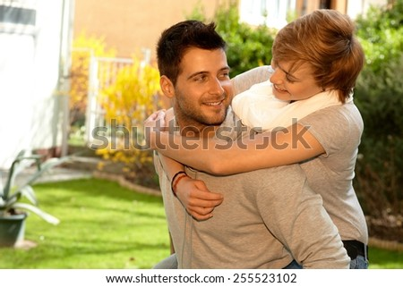 Happy loving couple having fun outdoors. Hugging, smiling. - stock photo