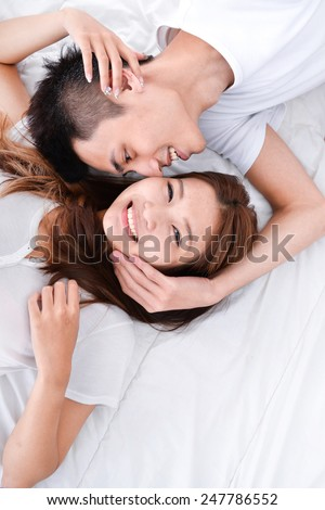 Happy loving couple in bed - stock photo