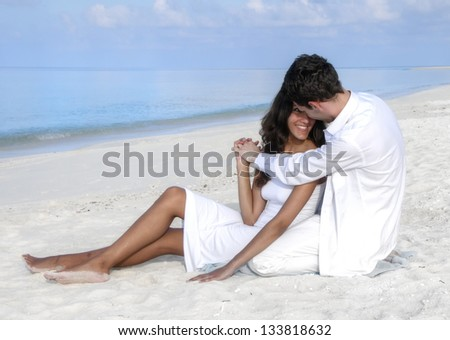 Happy loving couple in white clothes relaxing on the beach on Maldives