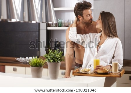 Happy loving couple kissing in the kitchen in the morning. - stock photo