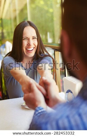 happy loving couple on date at the restaurant. young excited woman laughing and holding hands by man - stock photo