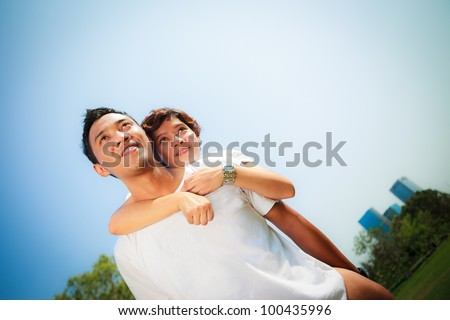 Happy loving couple playing in a park - stock photo