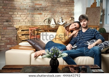 Happy loving couple sitting at home on sofa, relaxing.