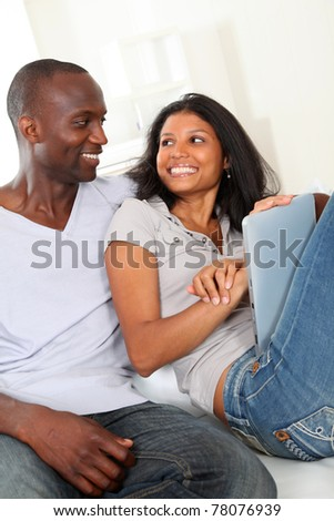 Happy loving couple sitting in sofa with electronic tablet