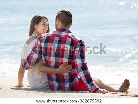 Happy loving couple spending free time at seaside in summer day - stock photo