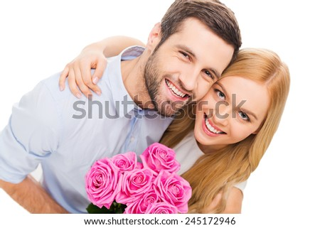 Happy loving couple. Top view of beautiful young loving couple bonding to each other and holding bouquet with pink flowers  - stock photo