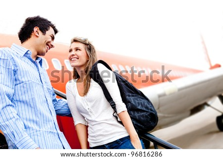 Happy loving couple traveling by airplane and smiling - stock photo