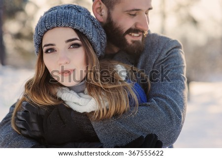 happy loving couple walking in snowy winter forest, spending christmas vacation together. Outdoor seasonal activities. Lifestyle capture.