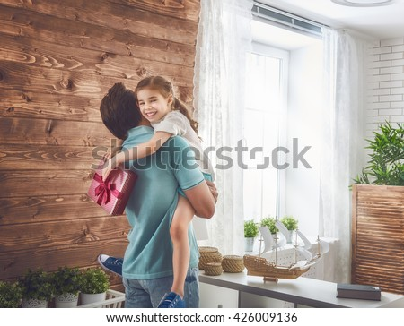 Happy loving family and Father's Day. Father and his daughter. Cute child girl gives a gift to dad. - stock photo